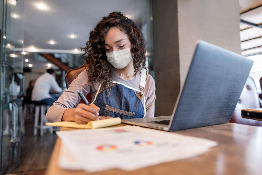 A business manager doing the books at a restaurant wearing a facemask.