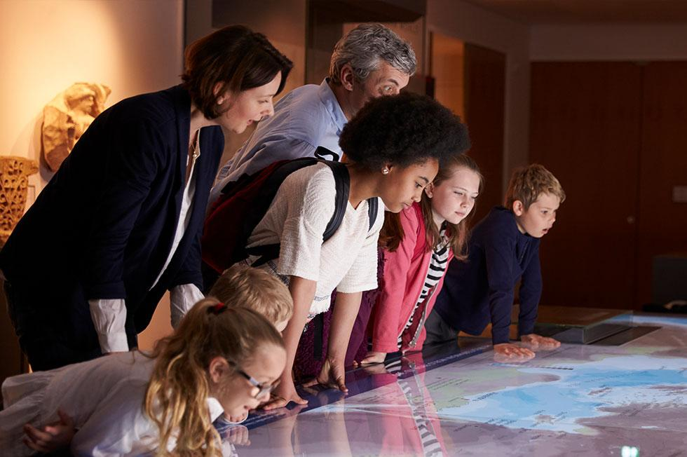 Group of students and adults looking at a map.